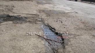Cratere, gunoaie si praf pe o strada din Iasi