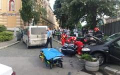 FOTO Tanara ranita dupa ce o masina a ajuns pe trotuar, dupa ce s-a ciocnit cu un alt autoturism, in fata Teatrului National din Cluj-Napoca