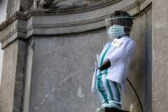 Faimoasa statuie Manneken Pis, imbracata in haine de medic, in semn de omagiu pentru lucratorii din sistemul medical