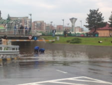 Inundatii la Valcea: Dorel asfalteaza o canalizare. Il ajuta si localnicii, cu o bancheta