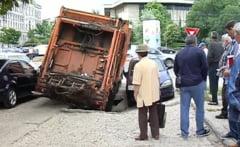 Masina de gunoi, inghitita de asfalt la Craiova