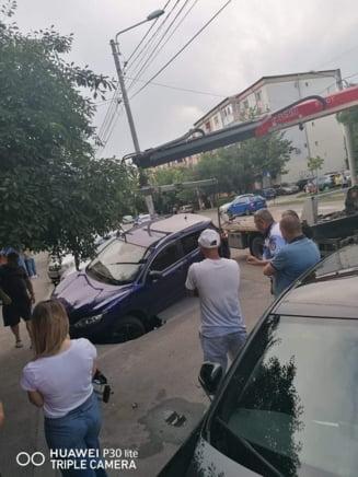 Masina suspendata intr-o groapa care a aparut din senin in asfalt in Craiova VIDEO