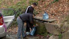 Mii de baimareni se inghesuie la apa de izvor nepotabila, desi la robinete e buna