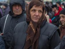 O femeie obosita si infrigurata, venita tocmai de la Pascani, asteapta sa se inchine