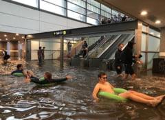 Ploaia le-a inundat pasajul prin care mergeau la lucru, asa ca si-au adus saltelele gonflabile si s-au distrat