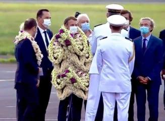 Povestea din spatele unei poze virale în care Emmanuel Macron apare împodobit cu ghirlande de flori în timpul unei vizite oficiale