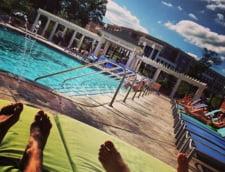 Studenti care se relaxeaza la piscina din campus