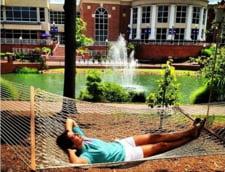 Un tanar student se relaxeaza intr-un hamac din campusul universitar