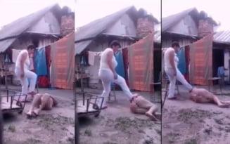 VIDEO Imagini socante din gospodaria groazei: o batrana neajutorata, dezbracata si cazuta in noroi este batuta de o femeie, in curtea unei case
